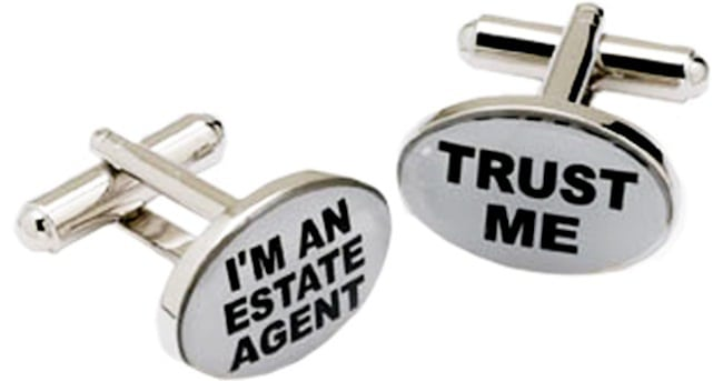 A pair of cuff links with Trust Me I'm an Estate Agent Engraved